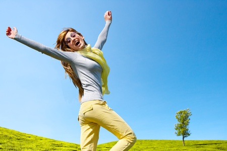 victorious: Energetic girl jumping with open arms outdoors. Stock Photo