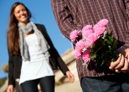 Boy holding flowers behind back with girlfriend approaching outdoors. photo