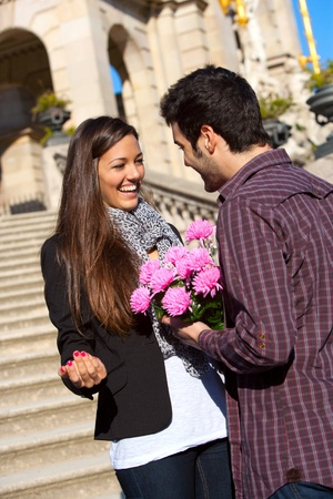 Boy surprising his cute girlfriend with pink flowers on date outdoors. Stock Photo - 13112161