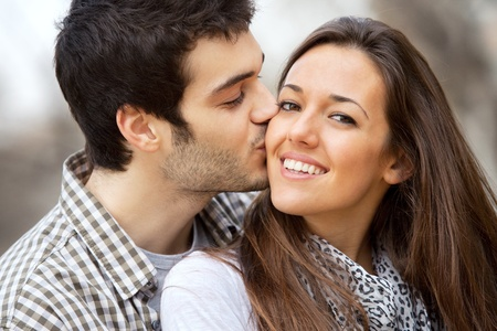 couple cuddling: Close up portrait of boy kissing girlfriend on cheek outdoors
