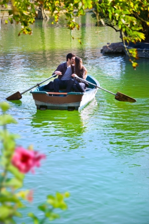 Romantic young couple boating on calm lake   Stockfoto