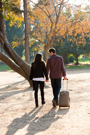 gentlemen: Young Couple walking together in park with traveling trolley