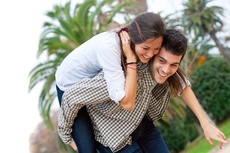 Attractive young girl piggybacking on boyfriend outdoors  Stock Photo - 13112169