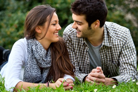 approachable: Close up portrait of handsome young couple laying on grass outdoors  Stock Photo