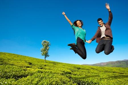 幸せなカップルが手を上げて、緑の野原とジャンプ