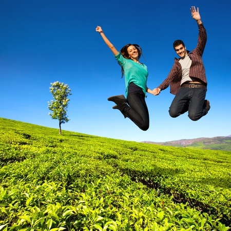 Jumping couple with hands raised in sunny green field  photo