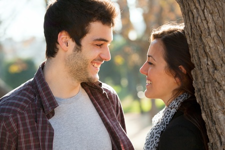 Close up portrait of young romantic couple in outdoor park