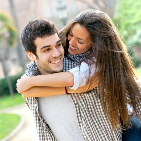 uomo felice: Close up ritratto di giovane coppia attraente all'aperto piggybacking Archivio Fotografico