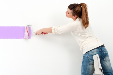 wall painting: Portrait of cute female painter painting the wall with color paint