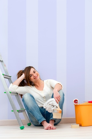 Portrait of cute female painter sitting on floor after painting  photo