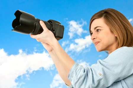 Young woman with big camera taking pictures outdoors  photo