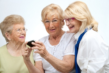 Portrait of three elderly senior woman holding cell phone Isolated on white Stock Photo - 13294579