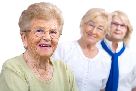 retiring: Close up portrait of friendly senior woman with girlfriends in background Isolated on white