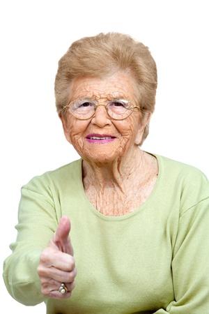 assentiment: Close up portrait de femme �g�e sympathique montrant thumbs up isol� sur blanc