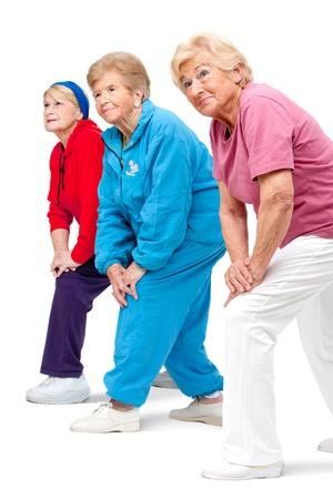 senior exercising: Threesome group of senior women doing stretching exercise Isolated on white