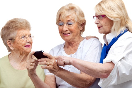 nineties: Close up portrait of three happy elderly women with cellphone Isolated on white