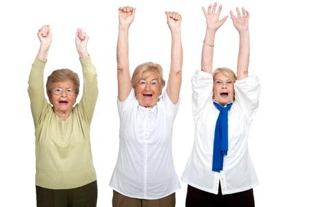 senior women: Portrait of three friendly senior women raising hands Isolated on white