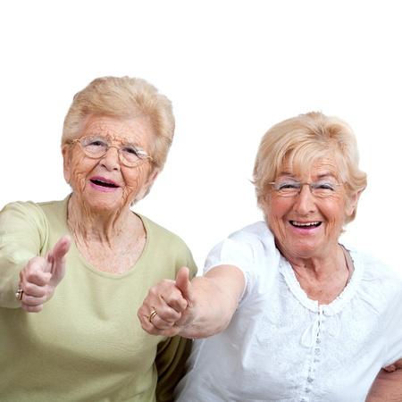 tercera edad: Close up retrato de dos mujeres amigas de alto nivel que muestran los pulgares para arriba aislados en blanco Foto de archivo