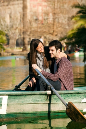 Happy romantic couple rowing a small boat on lake. photo