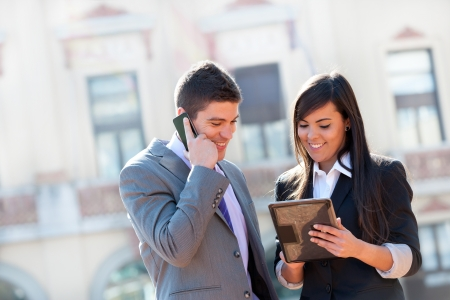 financial executive: Young Business couple working outdoors with digital tablet. Stock Photo
