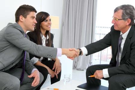 financial planner: Business couple shaking hands with financial planner.