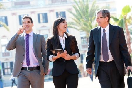 amigas conversando: Dynamic Business Team riendo de reunión al aire libre. Foto de archivo