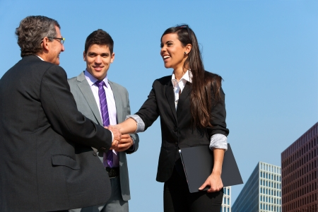 casual meeting: Young business couple shaking hands with partner outdoors. Stock Photo
