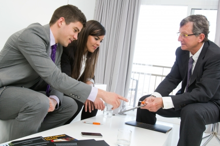 catalogs: Business threesome at finalcial meeting with documents and tablet on table. Stock Photo
