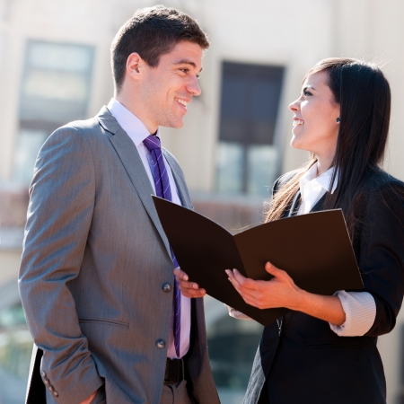 coworker: Close up of young business couple with file outdoors.