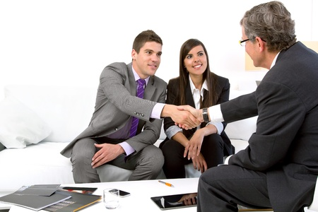 associates: Young attractive couple meeting with financial planner.  Stock Photo