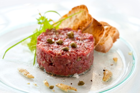 Close up of beef tartar with capers and small toasts. photo