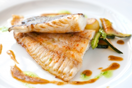 Close up of grilled brill fish with vegetables. photo