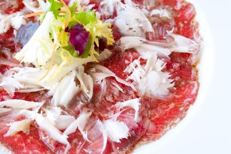 carpaccio: Close up macro of beef carpaccio with parmesan cheese flocks.