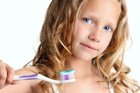 Close up Portrait of cute little girl holding toothbrush  Isolated on white background  photo
