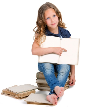 Cute girl sitting on pile of old books Pointing with finger on blank copy space  Stock Photo - 13976313