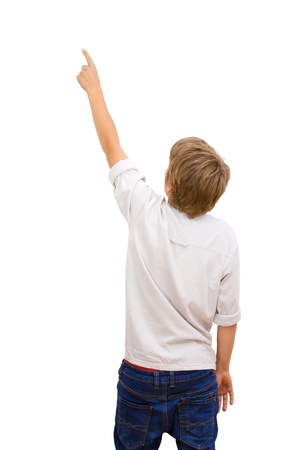 facing away: Boy facing backwards and pointing with finger at copy space Isolated on white
