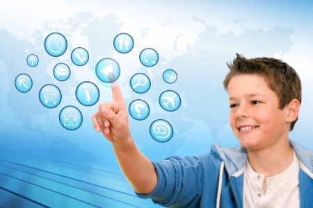 educational: Portrait of Boy pointing at web icons with futuristic interface  Stock Photo