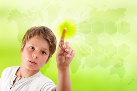 Boy touching futuristic green interface with green background and world map  photo