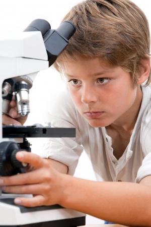 schooler: Close up ritratto di ragazzo con microscopio isolati su bianco Archivio Fotografico