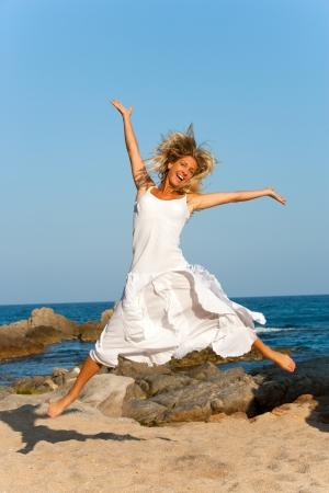 glädje: Attraktiv kvinna i vit klänning hoppar utomhus