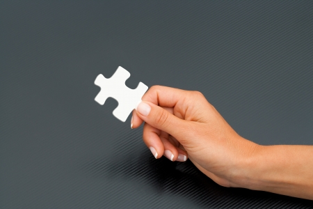 Close up of female hand holding white puzzle piece  photo