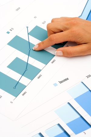 Close up of female hand on financial graphics Stock Photo - 14260557