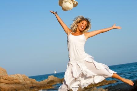 persona saltando: Mujer joven feliz en vestido blanco saltando en la playa Foto de archivo