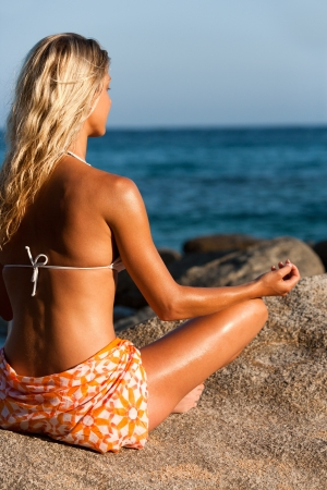 Young attractive woman doing yoga in late afternoon sun at seaside  Stock Photo - 14260479