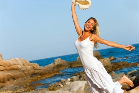 woman beach dress: Happy woman in white dress jumping on beach