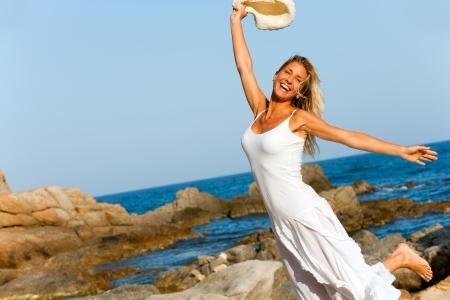glädje: Lycklig kvinna i vit klänning hoppning på stranden Stockfoto