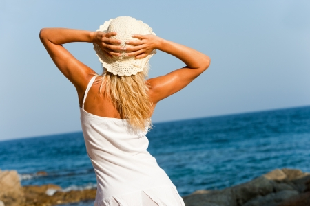 remoteness: Young woman in white dress looking at the sea  Stock Photo