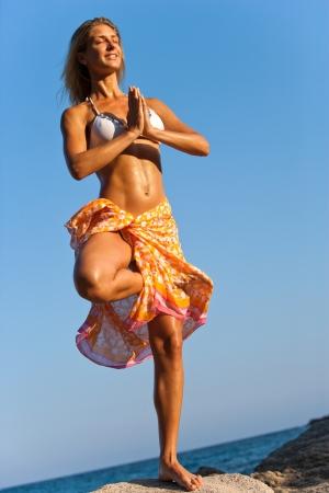 Young attractive woman in Hawaiian lei meditating at seaside  photo