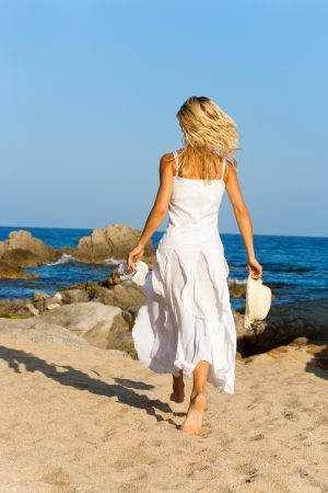 Young woman in white dress running on beach  photo
