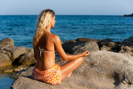 Young attractive woman meditating in late afternoon sun at seaside  photo
